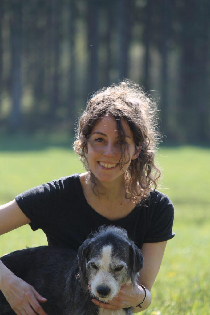 Hundetrainerin Britt Hundqvist im Portrait mit einem Hund im Vordergrund.